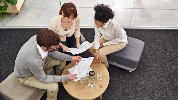 Three people sitting next to a coffee table looking over papers