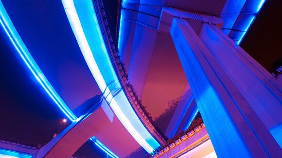 Ground view of 3 highway overpasses crossing on top of one another at night with blue and orange neon lights