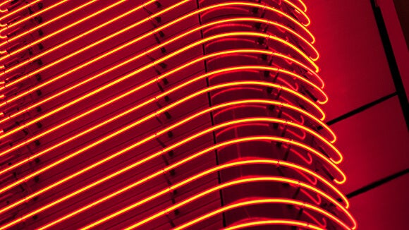 Red building with rows of thin orange neon light strips