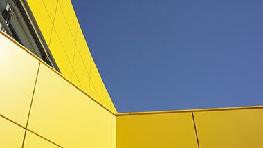 Yellow modern building against a blue sky