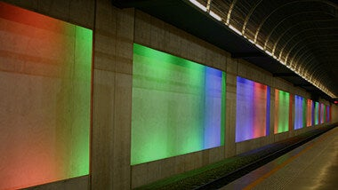 Underground subway rail with multicolored neon lights in against the left wall