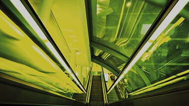 Green and neon lit underground tunnel escalator with glass ceiling