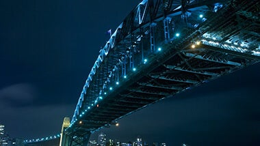 Tall city bridge with neon lights lit up in at night
