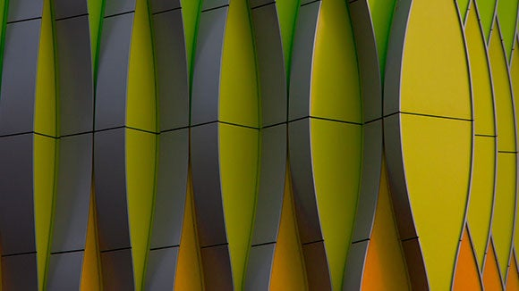 Modern structure with columns of abstract 3D rhombic orange, green and yellow colored walls