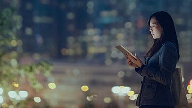 Woman in professional attire standing in a city street at night looking at her ipad
