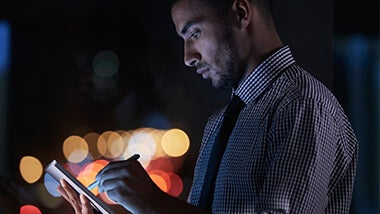 Man working on his tablet in the dark