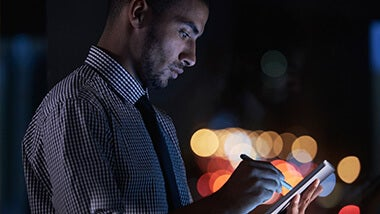 Man standing outside at night looking and writing on his ipad with a pen with night lights in the background